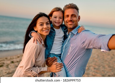 Happy family concept. Young attractive mother, handsome father and their little cute daughter standing together on the beach and making selfie.