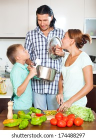 Happy family cooking with fresh vegetables at home kitchen