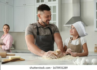 Happy family cooking together in kitchen at home