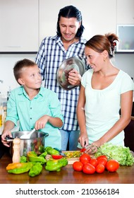 Happy family cooking veggie lunch with fresh vegetables and greens in home kitchen