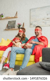 happy family in costumes of superheroes sitting on sofa with popcorn and watching tv