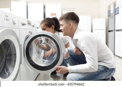 Happy family couple buying new washing machine in store