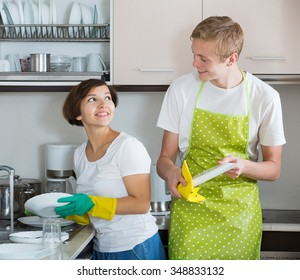 Happy family couple doing and wiping dishes after dinner
