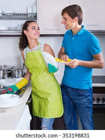 Happy family couple doing and wiping dishes after dinner in house