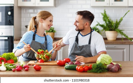 happy family couple preparing vegetable salad in the kitchen