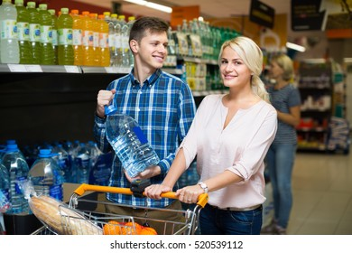Happy family couple purchasing mineral water