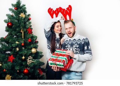 happy family couple in sweaters with gifs near christmas tree