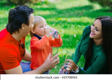 Happy family couple of young pretty woman and handsome man in park with son drinking water from glasses and smiling on green grass
