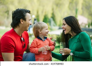 Happy family couple of young pretty woman and handsome man in park with son holding glasses of water and smiling sunny day