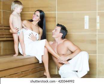 Happy family couple of young smiling woman and muscular man with son sitting in bath sauna in white towels