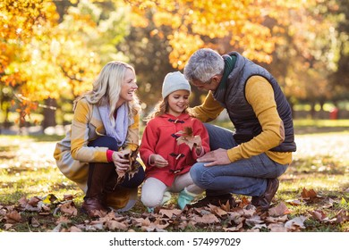 Happy family crouching against trees at park during autumn
