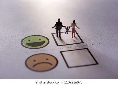 Happy Family Customer Concept. present by Miniature Figure of Father, Mother and Son in Happiness Moment. Walking on a Checked Box of Smiley Cartoon Face