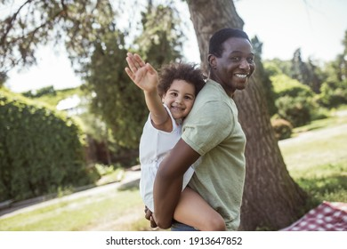 Happy family. Cute curly kid sitting on her dads back and smiling