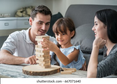 Happy family and cute little girl excites with wooden block game (Jenga) at home, selective focus