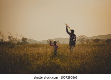 happy family dad and child run on meadow with a kite in the summer on the nature