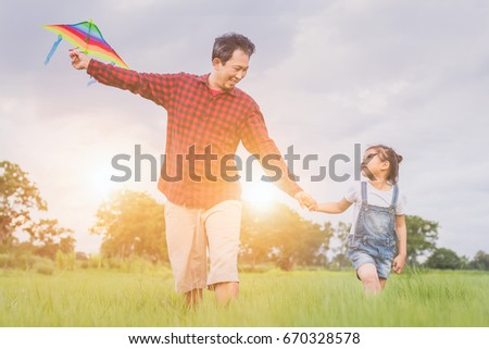 dc953de8 happy family dad and child run on meadow with a kite in the summer on the