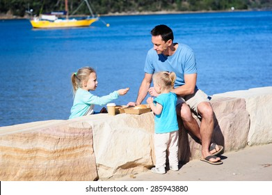 A happy family- dad or father and his young children sitting on the rock border and enjoying some food on a sunny summer day with the sea and boats in the background