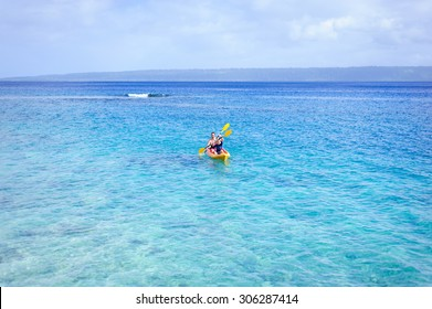 A happy family: dad and his children- a boy and a girl kayaking in the blue waters of the ocean