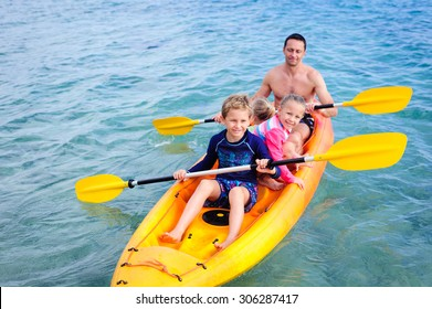 A happy family: dad and his children- a boy and two girls kayaking in the blue waters of the ocean