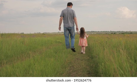 Happy family dad and little daughter walk holding hands in park on green grass. Daddy and baby are happy walking at sunset. Dad has weekend walk with his beloved daughter. Family, health and childhood