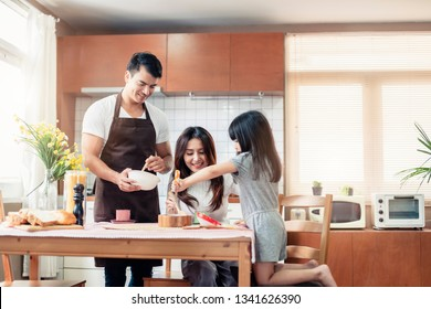 happy family dad mom and daughter mixed race happy prepare bakery in kitchen home background