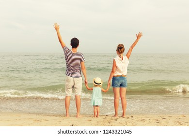 Happy family! Dad, mother and daughter are standing on the seashore. Back view.