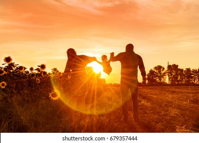 Happy family dad pregnant mom playing in the fresh air on the field near the sunflowers watching the beautiful emotional sunset in the backlight