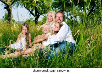 Happy family with daughter girls sitting in a meadow in summer