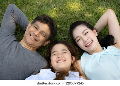 Happy family with  daughter laying on the lawn, top view