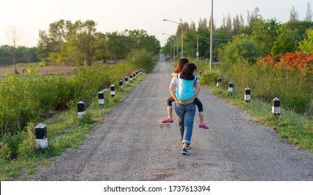 Happy family daughter Riding mom back Walking exercise on the road