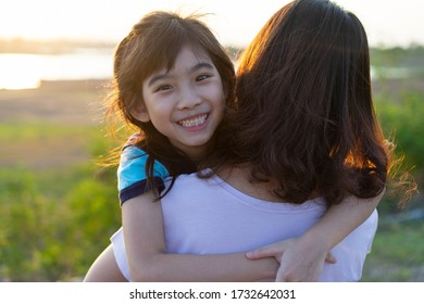 Happy family daughter Riding mother back On Trip smile Mountain reservoir Sunset view On holiday