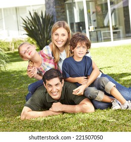 Happy family with daughter and son laying in a garden in front of house