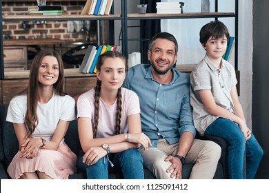 happy family with daughter and son sitting on sofa at home
