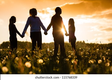 Happy family with daughters standing in the summer meadow at sunset