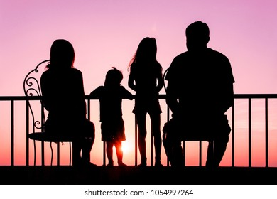 Happy family at the dawn of the sea silhouette background