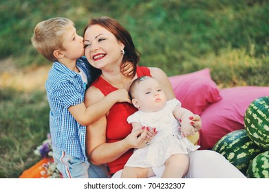 Happy family day, young mother with the children in summer city park, outdoor