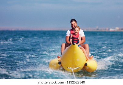 happy family, delighted father and son having fun, riding on banana boat during summer vacation