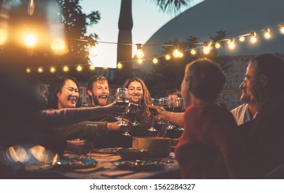 Happy family dining and tasting red wine glasses in barbecue dinner party - People with different ages and ethnicity having fun together - Youth and elderly parents and food weekend activities concept