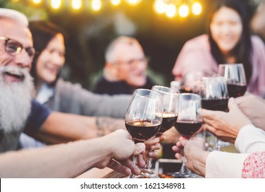 Happy family dining and toasting red wine glasses in barbecue dinner party - People having fun eating together - Youth and elderly parents and food weekend activities concept - Focus on first glass