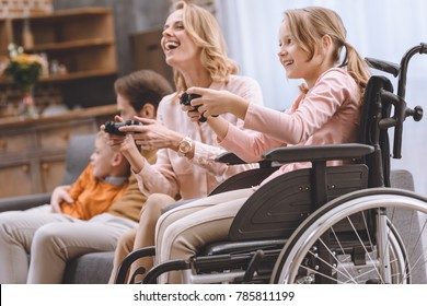 happy family with disabled child in wheelchair playing with joysticks together at home