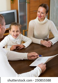 Happy family with documents at the table in living room