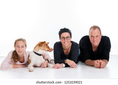 happy family with dog lying in front of white background