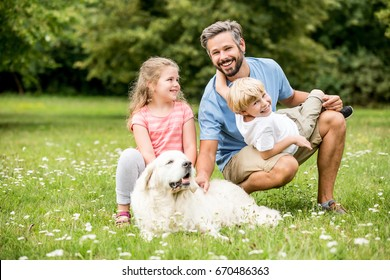 Happy family with dog Retriever in summer in the garden