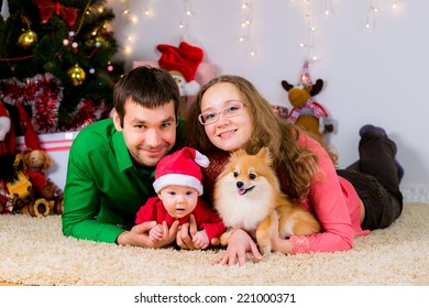 Happy family and the dog spending Christmas time at home laying on the carpet near the Christmas tree.