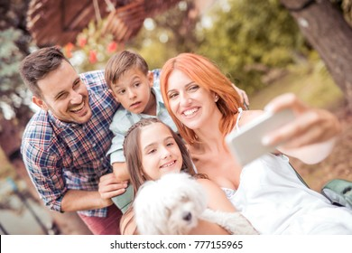 Happy family with dog taking selfie with smart phone in the park.Family,pet,technology and people concept.