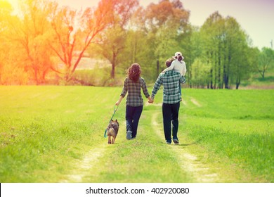 Happy family with dog walking on the rural dirt road. Little girl sitting on dad's shoulder