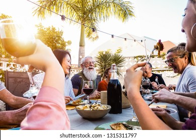 Happy family doing a dinner during sunset time outdoor - Group of diverse friends having fun dining together outside - Concept of lifestyle people, food and weekend activities