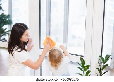 famille heureuse faisant le ménage de la maison. Jeune mère avec son bébé fils lavant les fenêtres ensemble