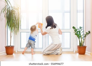 happy family doing the house cleaning. Young mother with her baby boy son washing windows together