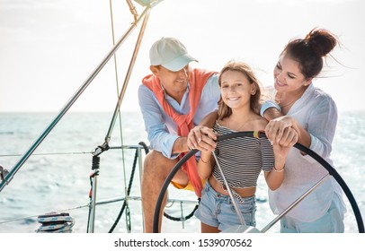 Happy family doing luxury sailboat trip - Father, mother and daughter having fun traveling in caribbean sea - Travel, love and vacation concept - Main focus on kid face